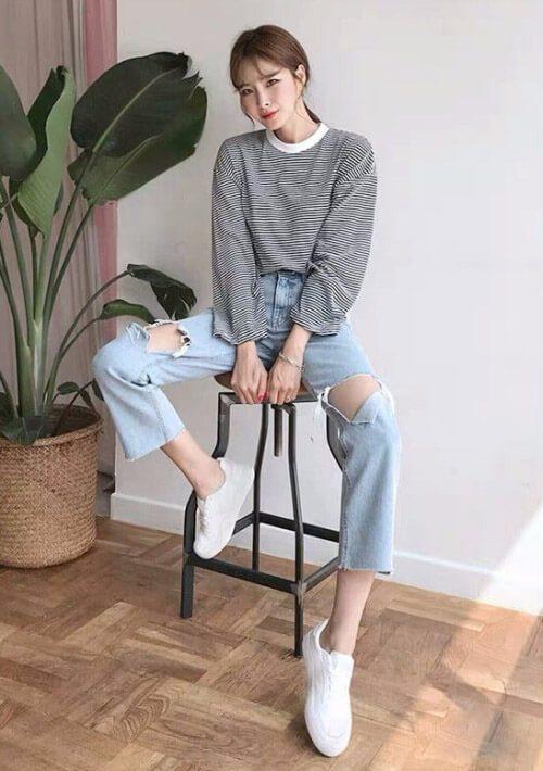 Cô gái ngồi trên ghế, áo phông dài tay,quần jean với giày trắng