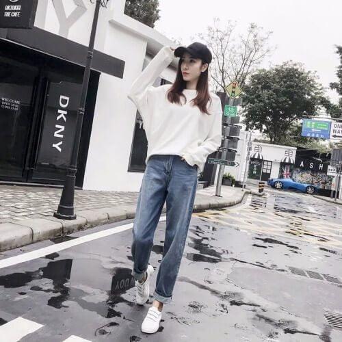 Cô gái mặc Áo len trắng + quần jean dài, có xắn quần + giày trắng